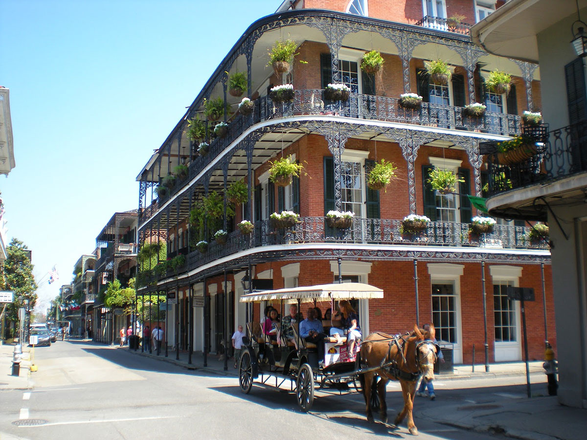 Horse-drawn wagon with tourists in thw French Quarter.
