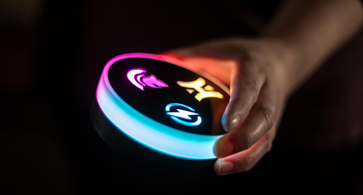 Ideum's next-gen Smart Tangible lights up in several colors in hand of user.