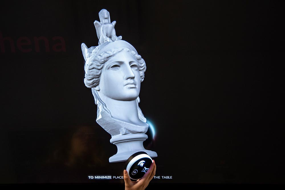 Tangible object held above a digital bust of Athena.