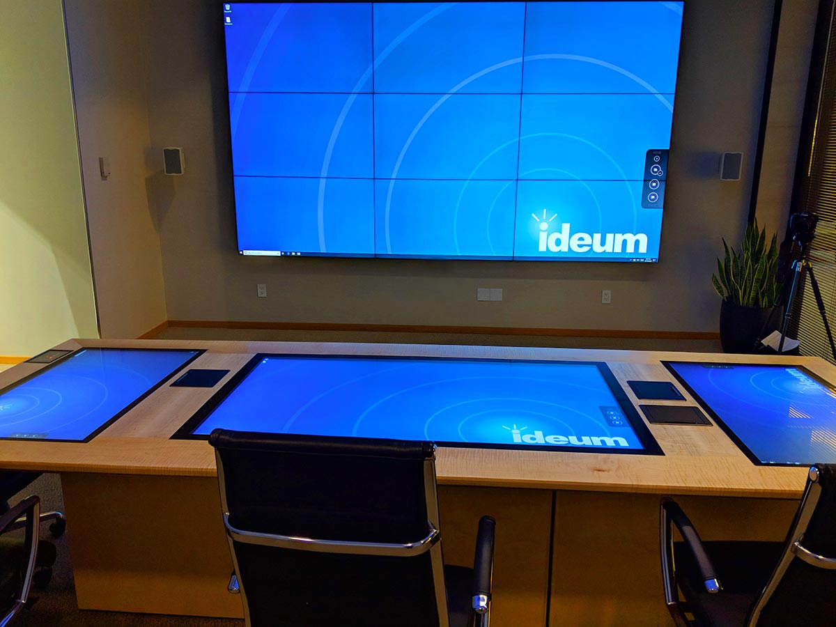 Three touch displays embedded in a long wooden conference table in a front of a large wall-mounted Crestron touch display.