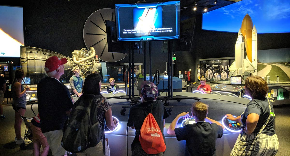 A group of people (kids and adults) stand at control consoles to answer multiple-choice space-related questions to compete for Flight Ready status.