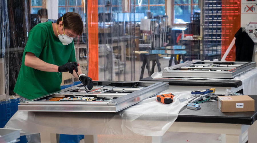 Ideum employee assembling multitouch table with appropriate personal protective equipment.