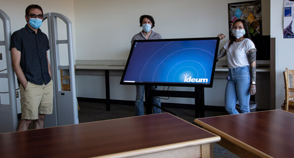 Ideum staff present an Ideum Presenter multitouch table on a motorized stand to Atrisco High School staff.