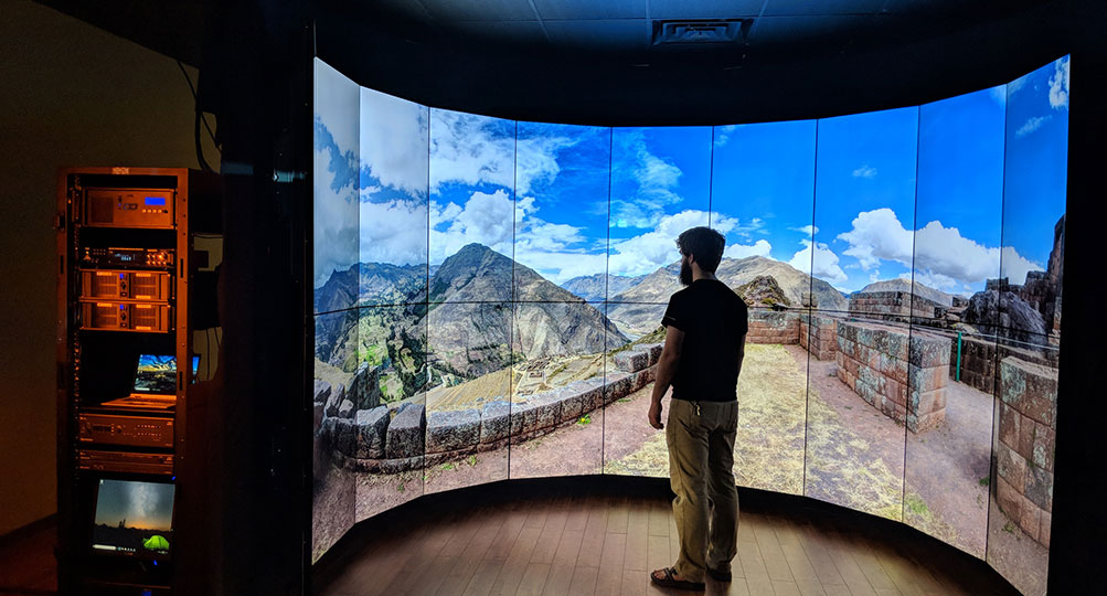 A man stands within the concave shape of an immersive video wall.